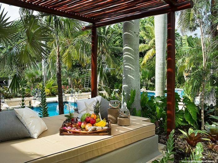 ein Pergolla, hohe Pflanzenq bequeme Loungemöbel, eine Platte voller Früchte, Gartenideen für wenig Geld
