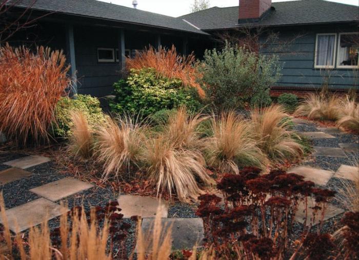 viele Zierpflanzen, Gartenweg aus Steinen. ein Hinterhof, rote Akzente, Gardenideen für wenig Geld