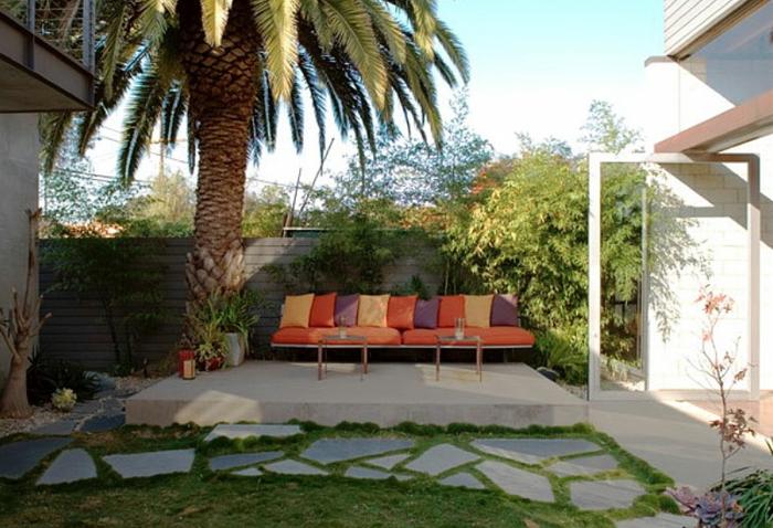 ein grüner Rasen im Hinterhof, orange, gelbe und lila Kissen auf dem Gartensofa, Gartenideen für wenig Geld