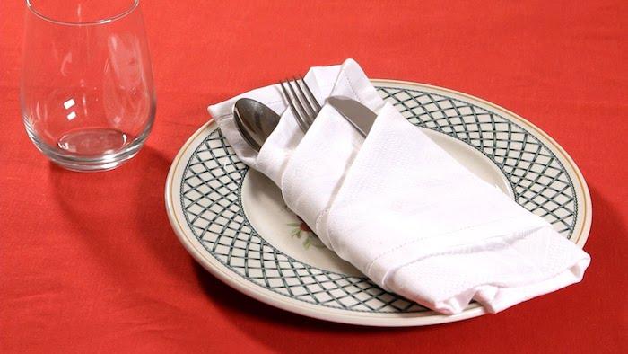 ein glas und ein weißer teller mit einer weißen bestecktasche mit einem löffel, einem messer und einer gabel, ein tisch mit einer roten decke, bestecktasche falten