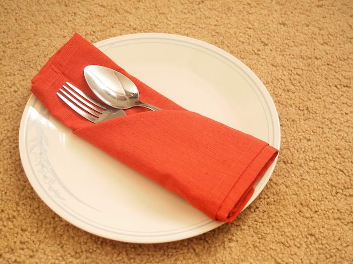 ein weißer teller mit einer kleinen orangen serviette mit einem löffel und einer gabel aus metall, eine bestecktasche falten