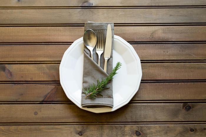 ein tisch aus holz mit einem weißen teller mit einer grauen serviette mit einem messer, einem löffel und einer gabel und mit grünen pflanzen, servietten falten einfach und wirkungsvoll