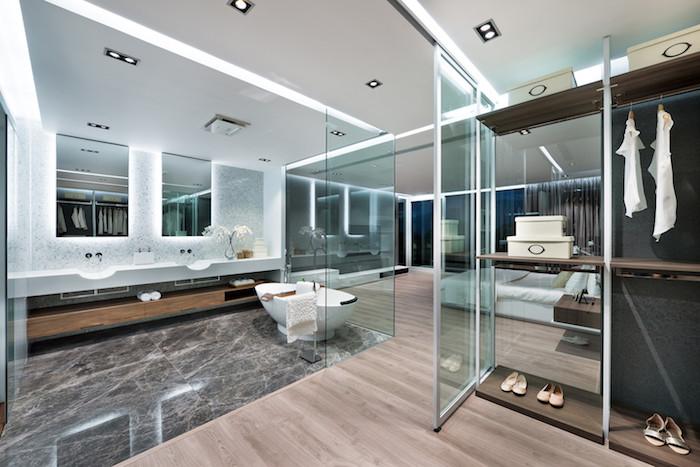 ein großes badezimmer mit zwei spiegeln und mit einem waschbecken und mit einem braunen boden aus holz und schuhen und kleidern und lampen und einer weißen badewanne