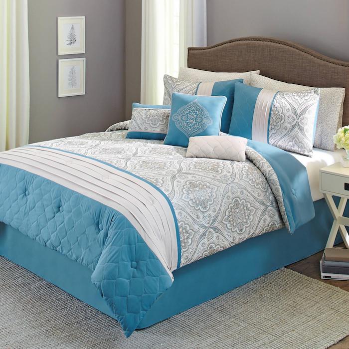 ein grauer teppich und ein blaues bett mit vielen kleinen und großen blauen und grauen kissen, ein kleiner weißer tisch aus holz und mit einer kleinen weißen vase mit gelben blumen, ein schlafzimmer einrichten, eine graue wand mit zwei weißen bildermn mit schwarzen bäumen