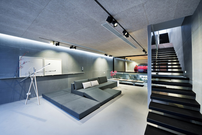 eine lange schwarze treppe, ein haus einrichten, ein wohnzimmer mit grauen wänden und grauen sofas mit grauen und kleinen weißen kissen und mit einem roten wagen, eine wohnung einrichten