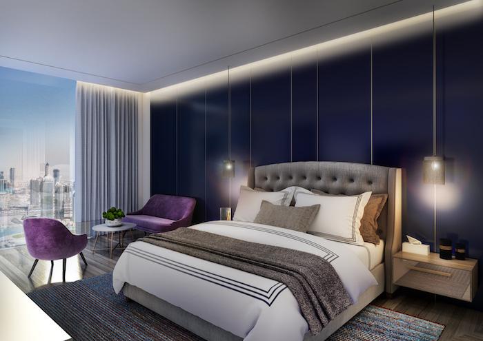 kleines schlafzimmer einrichten ideen, ein bett mit weißen, grauen und braunen kissen, ei kleiner weißer tisch mit einer weißen vase mit grünen pflangen und zwei violette stühle, eine große blaue wand und zwei lampen