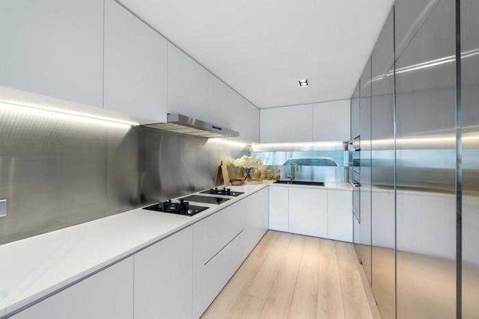 eine große weiße küche mit einem brauen boden aus holz und mit einem waschbecken und weißen möbeln, eine wohnung einrichten