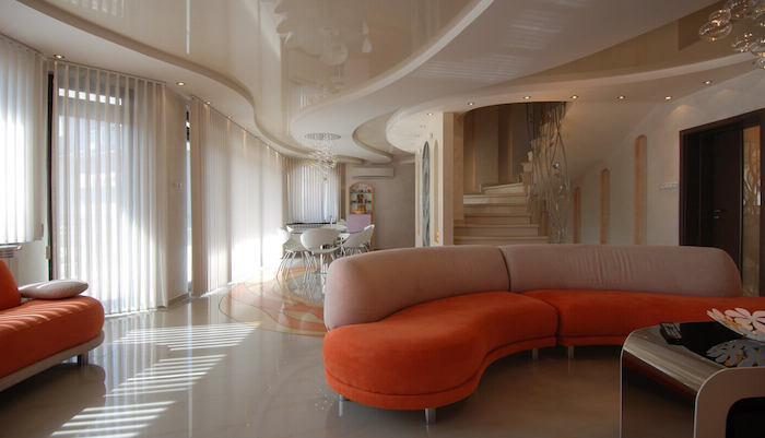 ein oranges sofa und ein wohnzimmer mit fenstern und weißen wänden, ein tisc und kleine weiße stühle, eine große weiße treppe und kleine gelbe lampen, zimmer einrichten ideen