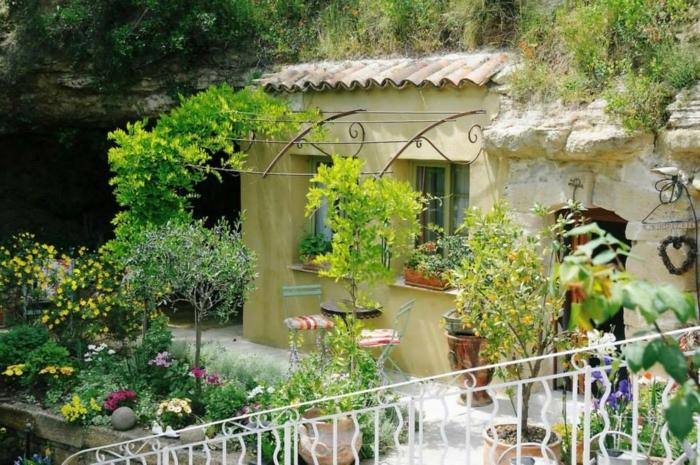 eine gelbe Wand, grüne Pflanzen, niedrige Bäume, weißer Gartenweg, günstige Gartengestaltung Ideen