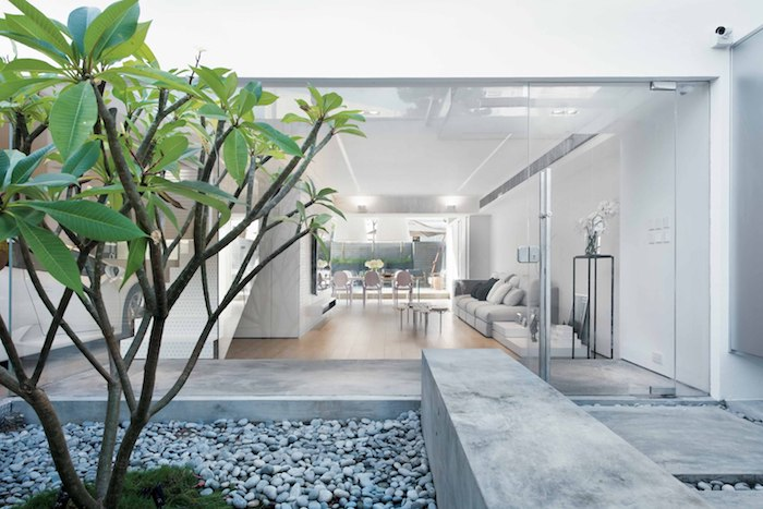 ein wohnzimmer mit einem boden aus holz und mit weißen wänden, einem weißen sofa mit graen und weißen kissen, ein kleiner garten mit einem baum mkt grpnen blättern und mit kleinen grauen steinen, ein hauns einrichten