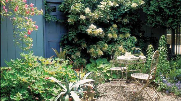weiße, gelbe und rosa Blumen, Ziersträuche, kleine Gartenmöbel, Kies Bodenbeleg, günstige Gestaltungsideen Garten