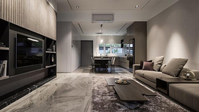einhaus einrichten, ein beiges wohnzimmer mit einem kleinen tisch aus holz und mit beigen sofas und einem schwarzen großen fernseher, ein tisch und stühle