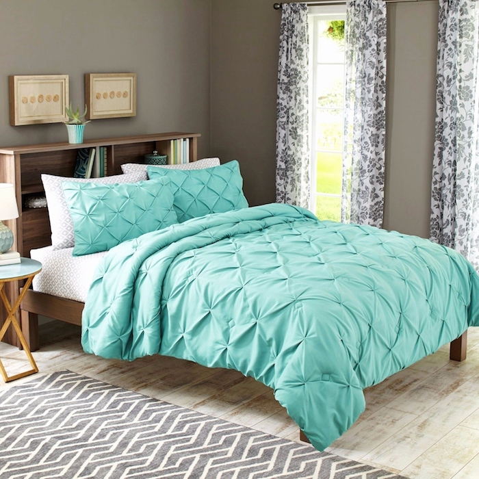 ein bett mit grünen und weißen kissen, ein boden aus holz und ein grauer teppich, eine wohnung mit grauen wändenund mit zwei fenstern
