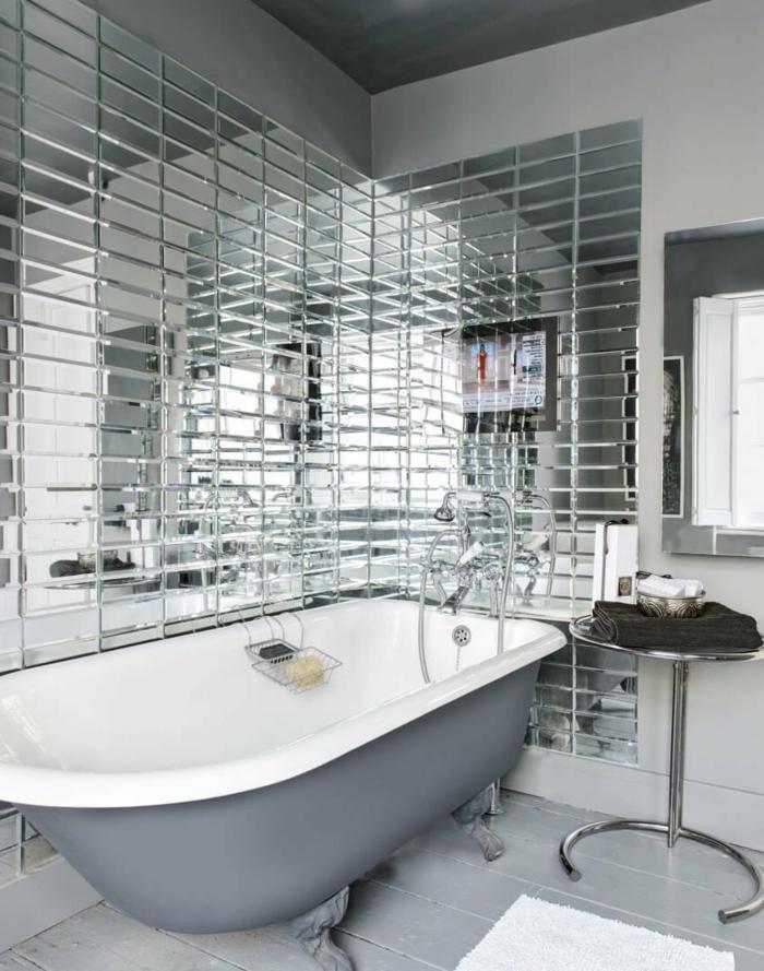 Fliesen, die wie Spiegel wiederspiegeln, eine ausgelassene Badewanne, graue Badefliesen, kleine Räume geschickt einrichten