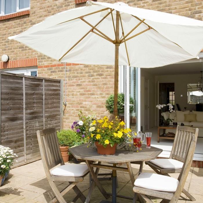 Gartenmöbel aus Holz, ein weißer Sonnenschirm, ein Zaun aus Holz, günstige Gartengestaltung Ideen