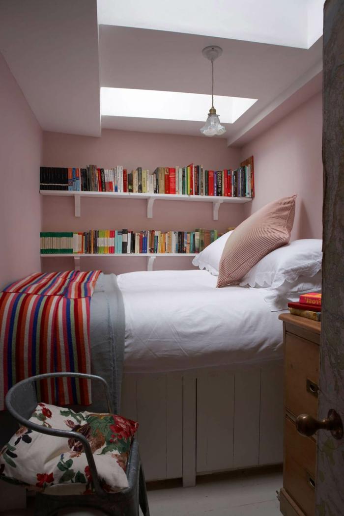 bunte Decke, verschiedene bunte Bücher, ein kleines Bett, ein Regal aus Holz