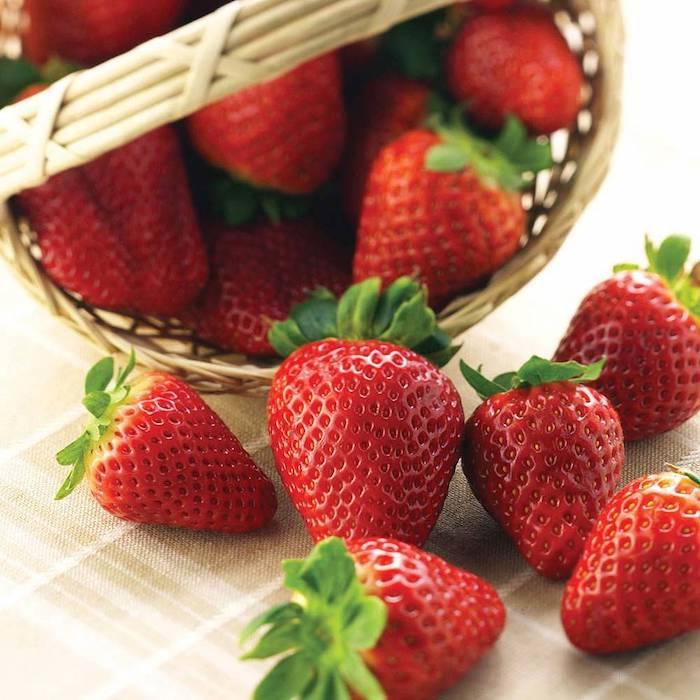 ein tisch mit einer beigen decke, ein kleiner korb aus rattan und mit vielen kleinen roten erdbeeren mit grünen blättern