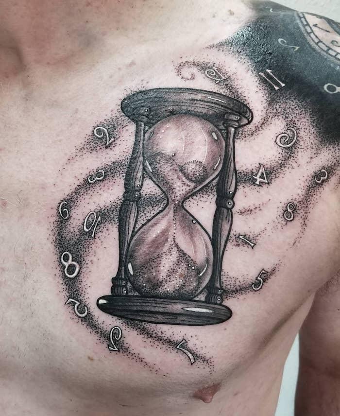 junger mann mit einem großen schwarzen tattoo mit einer schwarzen sanduhr aus holz und mit sand, tattoo mit vielen fluegenden tahlen, ein tattoo sanduhr, männer tattoos