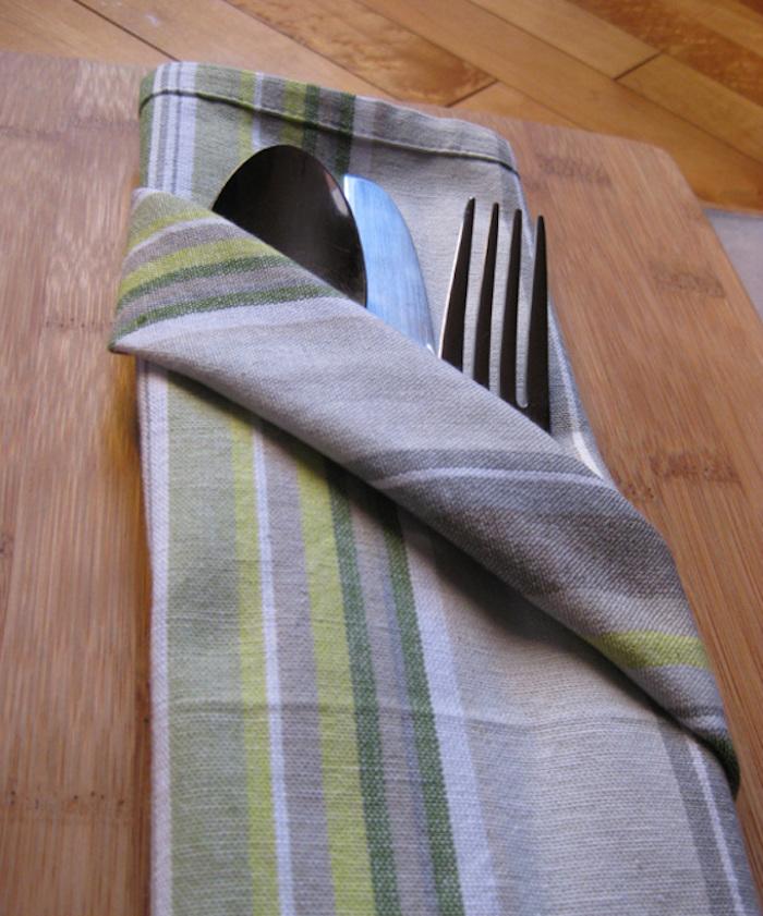 ein tisch aus holz, eine gefalteten bestecktasche mit einem messer, einem löffel und einer gabel, bestecktasche falten
