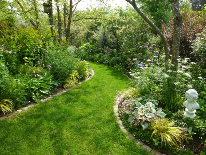 Garten Ideen günstig, Gartenweg aus Rasen, hohe Bäume, eine Figur als Gartendeko