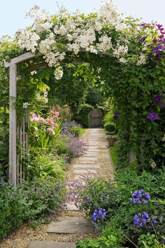 schöne Bögen mit weißen Blumen, blaue Blumen am Boden, Gartenweg mit Stein und Kies, Garten Ideen günstig
