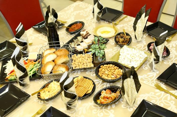 ein Tisch mit viel zu essen, Tischdecke mit weißen Blumenmustern, schwarze Teller
