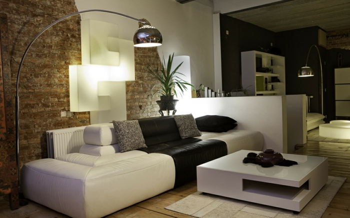 schwarz weißes Sofa, ein kleiner weißer Couchtisch, eine braune und weiße Wand, kleine Räume einrichten