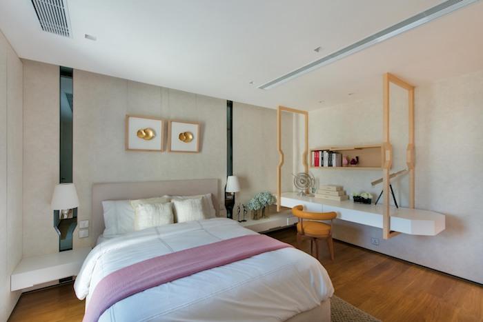 ein bett mit weißen und gelben kissen, ein kleines schlafzimmer einrichten mit zwei kleinen weißen lampen, eine vase mit grünen blumen und ein oranger stuhl, viele kleine bücher