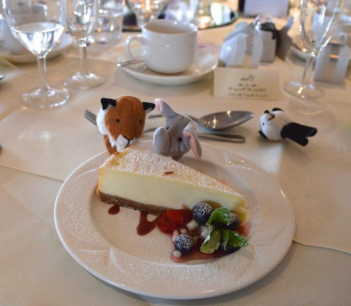 ein Stück süße Torte, kleine Kuscheltier wie Löwen, Elefanten und Panda, Kommunion Tischdekoration