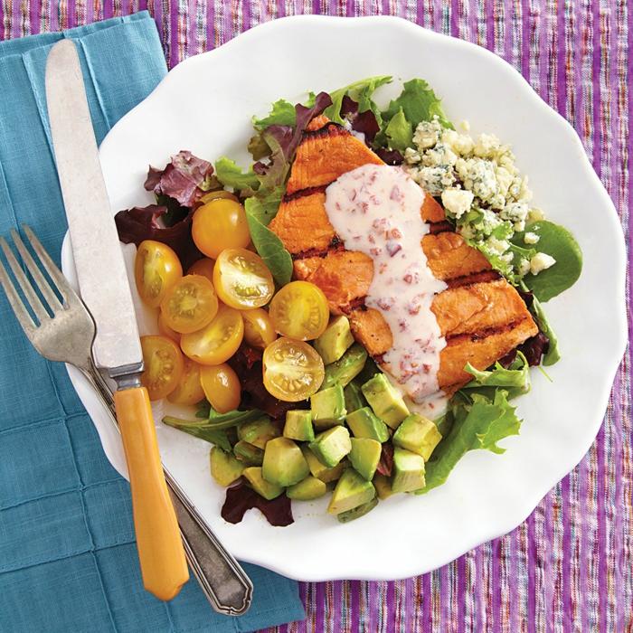 Avocado, gelbe Kirschtomaten, ein Steack, ausgefallene Salate für Grillparty mit rosa Dressing