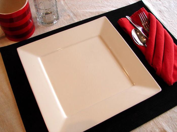 gläser und ein großer weißer teller, eine große rote bestecktasche mit einem löffel, einem messer und einer gabel aus metall, bestecktasche falten