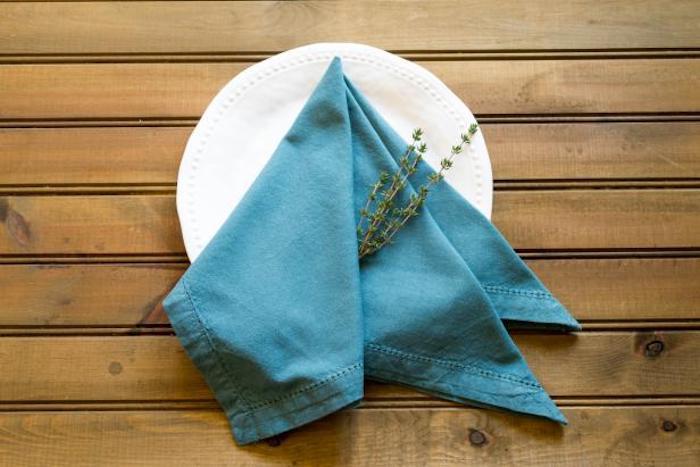 ein tisch aus holz, weißer teller mit einer großen blauen gefalteten serviette mit gr´nen pflanzen mit grünen blättern, servietten falten