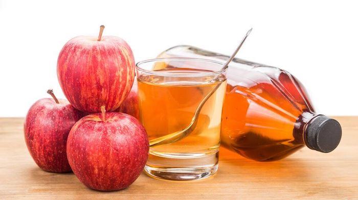 eine große braune flasche und ein glas mit einem orangen apfelessig und mit einem löffel, drei große rote äpfel und ein tisch aus holz., fruchtfliegenfalle essig