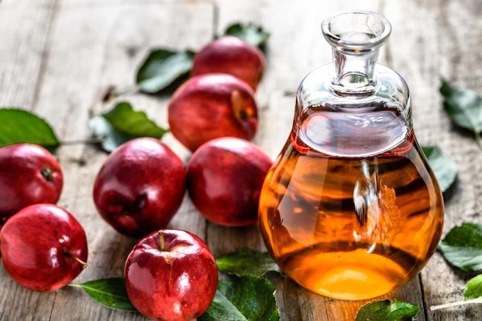eine kleine kanne aus glas und mit einem orangen apfelessig, ein tischa su holz und miz vielen roten äpfeln und grünen blättern, fruchtfliegenfalle diy