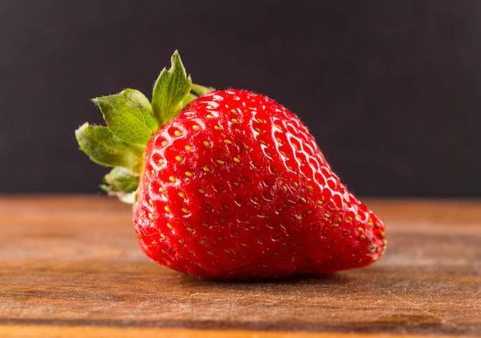 eine große rote erdbeere mit kleinen grünen blättern und ein tisch aus holz, eine fruchtfliegenfalle mit erdbeeren selber machen