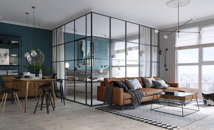 ein braunes sofa mit brauen, weißen und schwarzen kissen, ein tisch aus holz und kleine schwarze stühle, ei zimmer mit blauen und weißen wänden und mit einem boden aus holz, eine wohnung einrichten