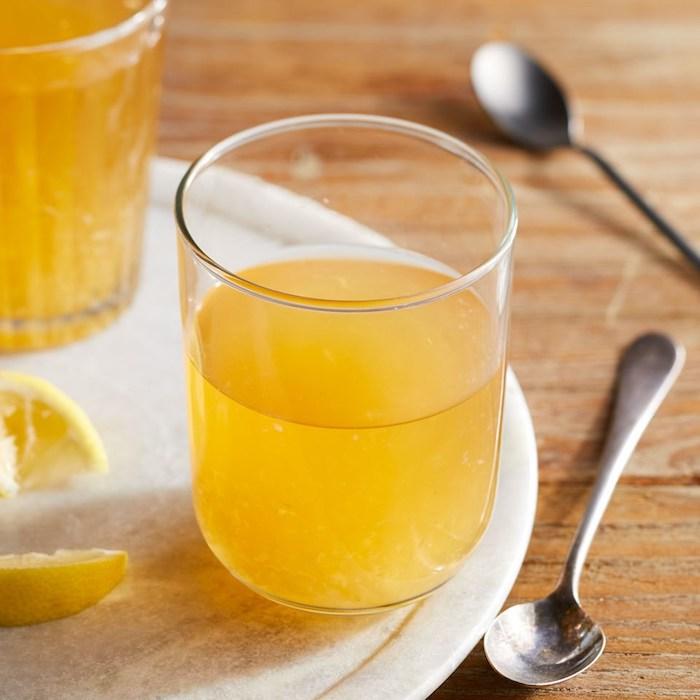 zwei löffel aus metall, ein isch aus holz, ein weißer teller mit zwei gläser mit einem gelben apfelessig und mit zitronen, fruchtfliegenfallen selber machen