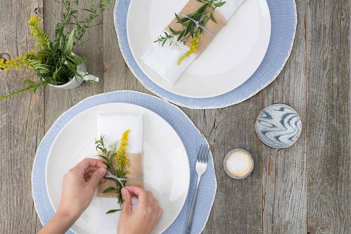 zwei hände, eine tischdekoration selber machen, zwei weiße teller mit weißen bestecktaschen mit gelben und grünen pflanzen und mit einer gabel, eine bestecktasche falten