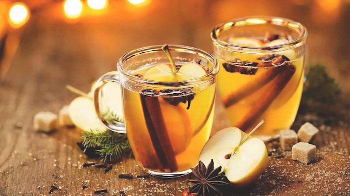 zwei gläser mit einem tee mit einem gelben apfelsaft und zimt und mit großen gelben äpfeln, ein tisch aus holz und äste mit grünen blättern und zucker, eine fruchtfliegenfalle essig
