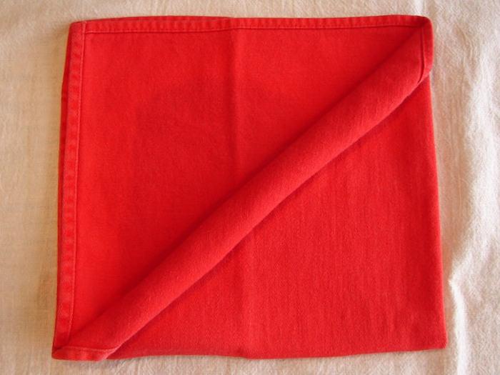 ein tisch mit einer gelben decke und mit einer großen roten serviette, servietten falten einfach und wirkungsvoll