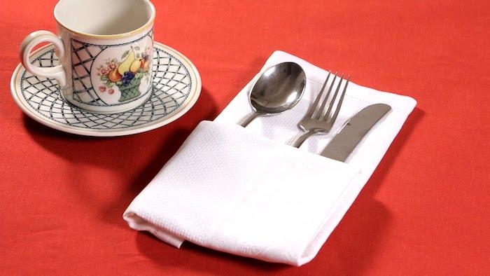 tisch mit einer roten decke, bestecktaschen falten, ein glas und eine weiße gefaltete bestecktasche mit einer gabel, einem löffel und einem messer