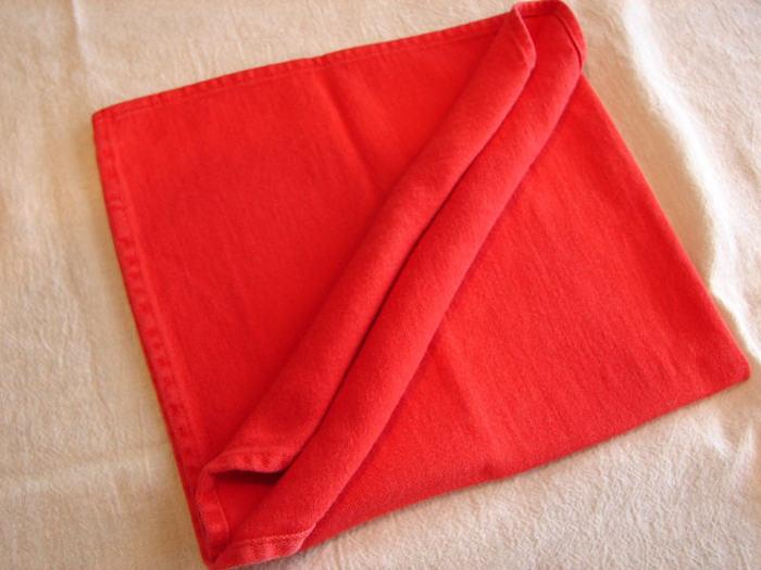 eine große rote gefaltete serviette und eine weiße decke, servietten falten einfach und wirkungsvoll