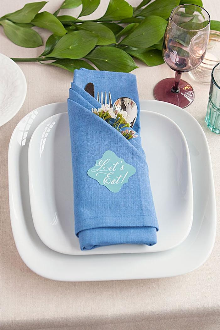 pflanzen mit großen grünen blättern, tischdekoration mit zwei weißen tellern, gläsern und einer gefalteten blauen bestecktasche mit einem löffel, einer gabel und einem messer und kleinen pinken blumen