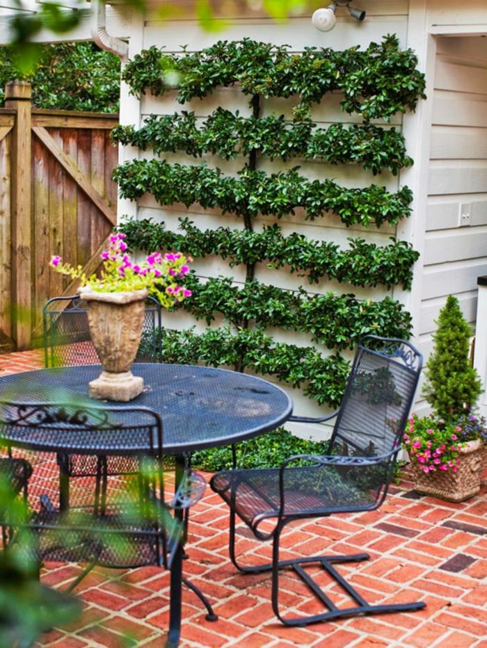 schöne blaue Gartenmöbel, ein vertikaler Garten, Vase mit rosa Blumen, Garten Ideen günstig