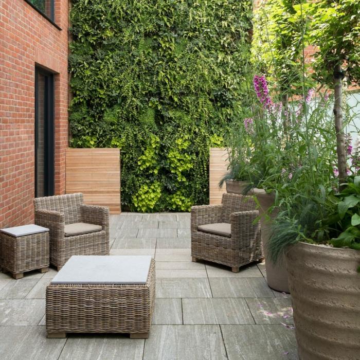 beige Gartenmöbel aus Rattan, ein vertikaler Garten an der Mauer, Sichtschutz aus Backteinen, Garten anlegen günstig
