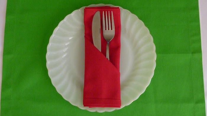 ein tisch mit einer grünen decke, ein großer weißer teller mit einer roten gefalteten serviette mit einem messer und euner gabel, eine bestecktasche falten