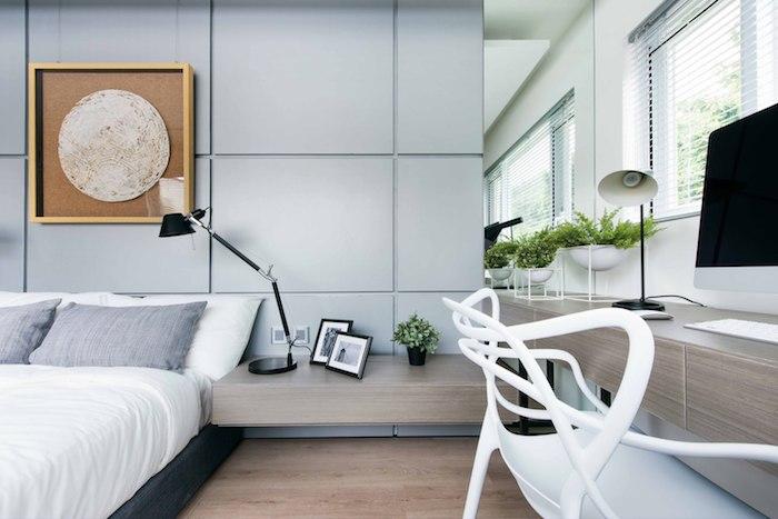ein großer weißer stuhl und ein bett mit grauen und weißen kissen, ein zimmer einrichten, eine kleine schwarze vase mit grünen pflanzen und blättern, eine schwarze lamoe und zwei bilderrahmen und ein boden aus holz