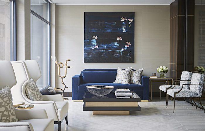 ein wohnzimmer mit einem blauen sofa mit zwei großen weißen kissen, eine große gelbe wand mit einem blauen bild, ein kleiner tisch und eine schüssel