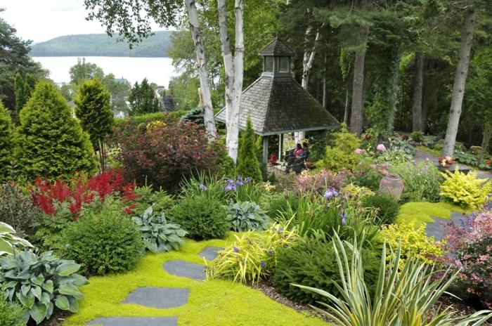 ein harmonischer Garten, grünes Grass, Beete mit bunten Blumen, ein Gartenpavillion, Garten anlegen günstig