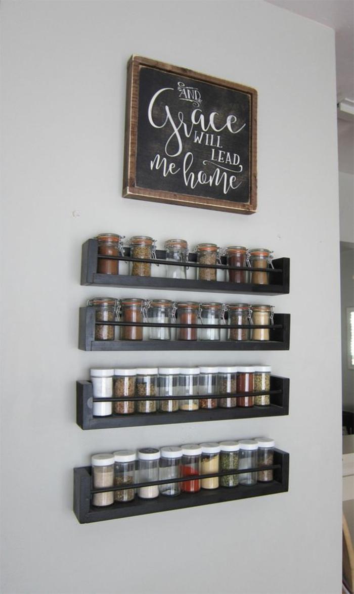 eine Tabelle mit interessanter Aufschrift, schwarze Regale mit Gewürzen, Küchenwand